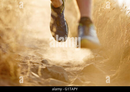 Close up of runner's feet on dirt trail - Stock Photo