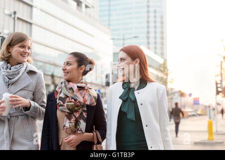 Businesswomen walking with coffee in city - Stock Photo