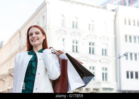 Smiling woman carrying shopping bags in city - Stock Photo