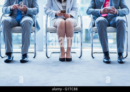 Business people with cell phones waiting in a row - Stock Photo
