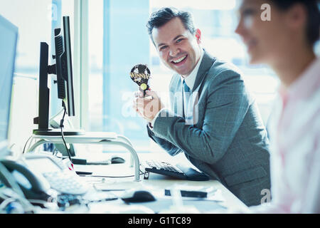 Portrait of enthusiastic businessman holding winner trophy at desk in office - Stock Photo