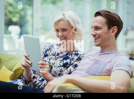 Couple using digital tablet on living room sofa - Stock Photo