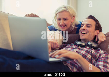 Smiling couple using laptop on living room sofa - Stock Photo