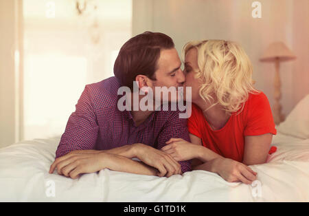 Couple kissing on bed - Stock Photo