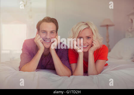 Portrait smiling couple with head in hands on bed - Stock Photo