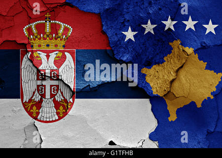 flags of Serbia and Kosovo painted on cracked wall - Stock Photo
