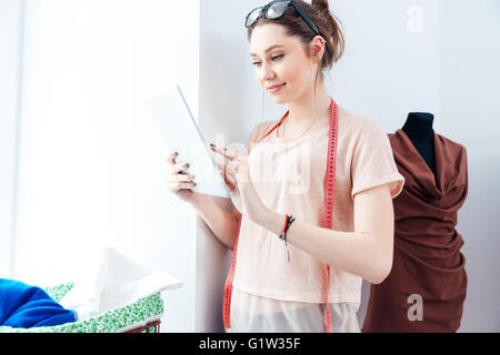 Smiling lovely young woman seamstress standing in design studio and using laptop - Stock Photo