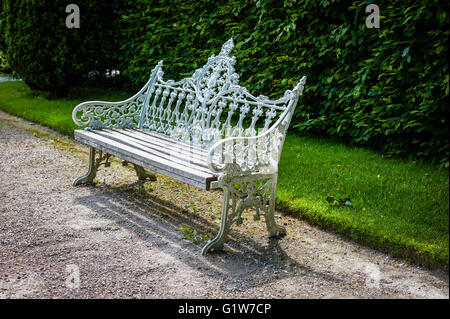 Old cast iron bench seat in garden open to the public in Cumbria UK - Stock Photo