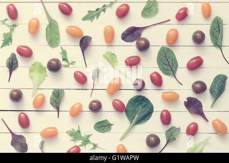 Food flat lay. Pattern of fresh greens and vegetables on white wooden background. Healthy eating concept - Stock Photo