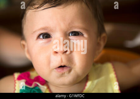 Close-up of one year old kid looking up with funny face - Stock Photo