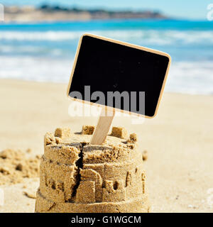 closeup of a sandcastle on the sand of a beach topped with a black blank signboard with a copy space - Stock Photo