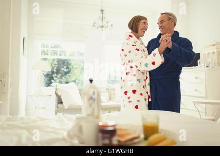 Mature couple dancing in bathrobes in bedroom - Stock Photo