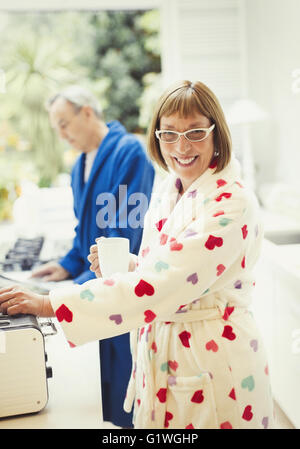 Portrait smiling mature woman drinking coffee in bathrobe at kitchen counter - Stock Photo