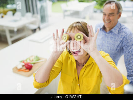 Portrait playful mature woman covering eyes with kiwi slices - Stock Photo
