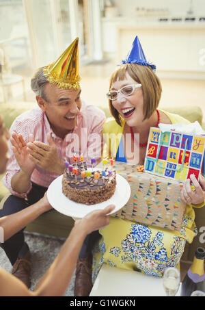 Smiling mature women receiving birthday cake and gifts - Stock Photo