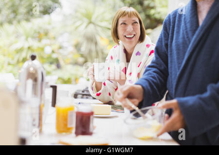 Smiling mature woman drinking coffee in bathrobe at breakfast - Stock Photo