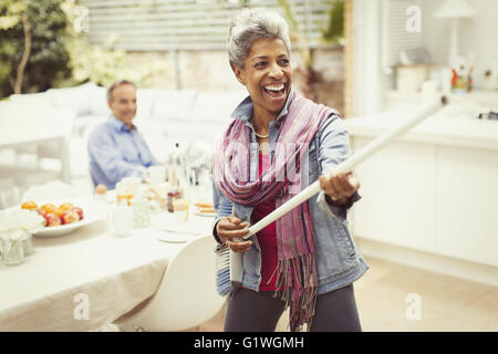 Portrait playful mature woman playing air guitar with stick in kitchen - Stock Photo