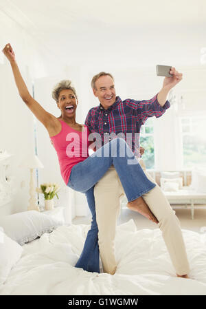 Playful mature couple taking selfie standing on bed - Stock Photo