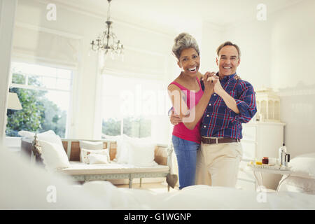 Portrait smiling mature couple dancing in bedroom - Stock Photo
