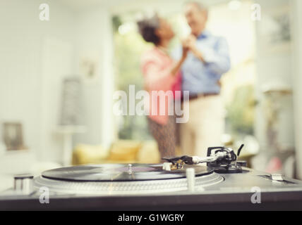 Mature couple dancing in living room behind record player - Stock Photo