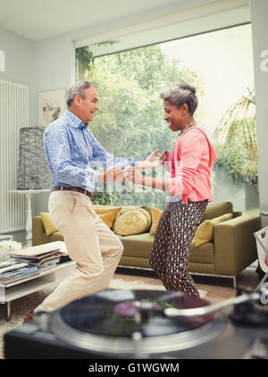 Playful mature couple dancing behind record player in living room - Stock Photo