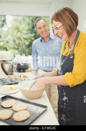 Mature couple baking cookies in kitchen - Stock Photo