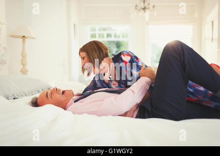 Well-dressed mature couple laughing on bed - Stock Photo