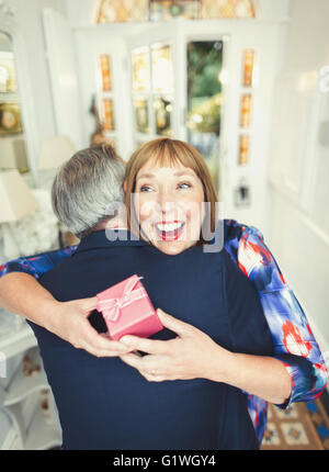 Surprise mature woman receiving gift from husband - Stock Photo