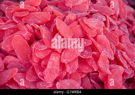 Heap of candied and dried tasty papaya slices with sugar for retail sale in food market. - Stock Photo