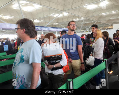 Passengers queuing for passport control at Stansted Airport Essex - Stock Photo