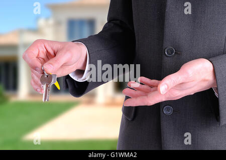 half lateral body commercial agent wearing a dark gray costume handing the keys for the purchase of a house with - Stock Photo