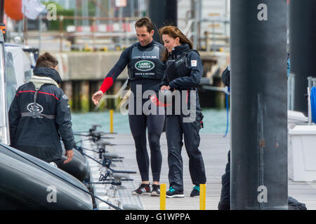 Sir Ben Ainslie guides The Duchess of Cambridge to a waiting boat at the BAR HQ at Portsmouth, UK on the 20th May - Stock Photo