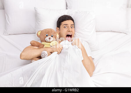 Top view of a terrified young man laying in bed with a teddy bear and screaming isolated on white background - Stock Photo