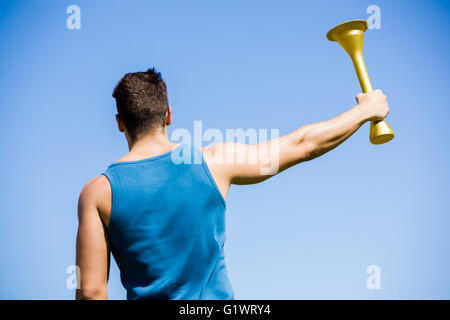 Athlete holding a fire torch - Stock Photo