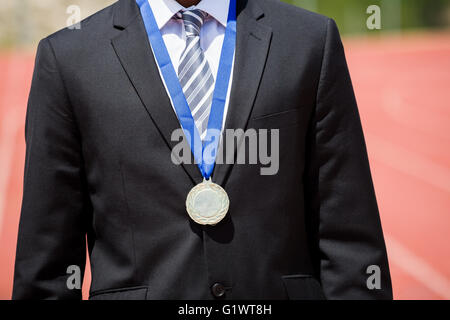 Businessman wearing gold medal - Stock Photo