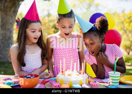 Portrait of cute girls preparing to blow on candle during a birthday party - Stock Photo