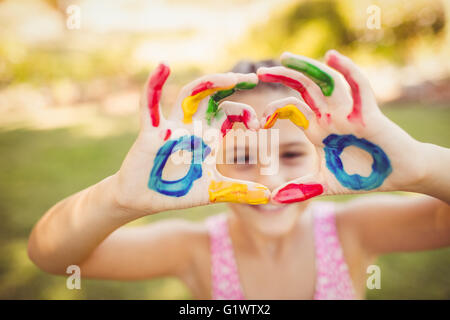 Girl making a heart with her painted arms - Stock Photo