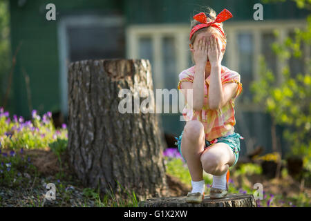 Cute little girl covering her eyes with her hands. See Nothing, Hear Nothing, Say Nothing To Anyone - a series of - Stock Photo