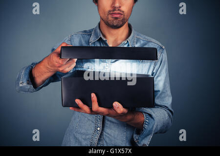 A young man is opening a box with something exciting inside it - Stock Photo