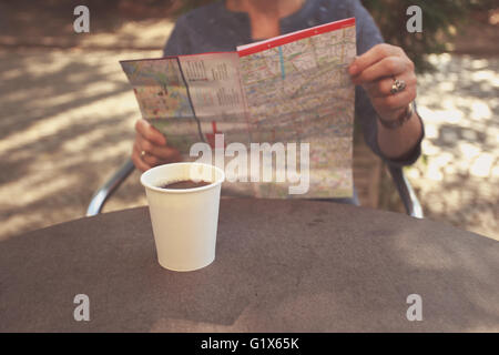 An elderly woman is sitting outside on a sunny day and is studying a city map whilst having coffee