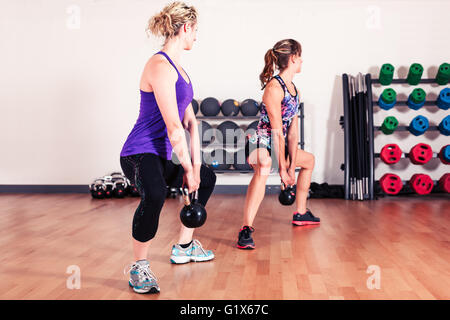 Two young women are working out with kettle bells in the gym - Stock Photo