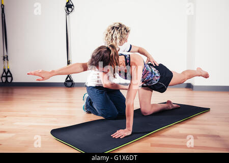 A therapist is correcting the technique of a woman exercising and stretching in a gym - Stock Photo