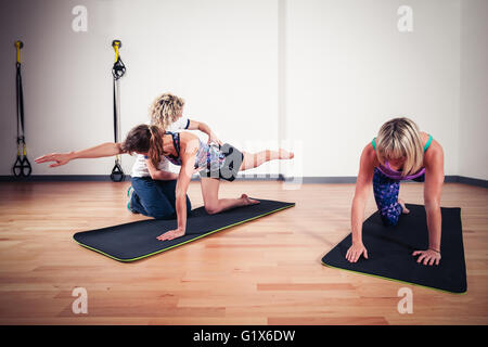 A therapist is correcting the technique of women exercising and stretching in a gym - Stock Photo