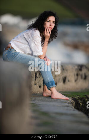 Loneliness: A young attractive slim brunette woman girl deep in thought,  sitting by herself, alone ,  outdoors - Stock Photo
