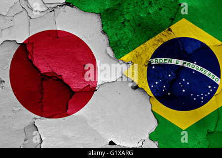 flags of Japan and Brazil painted on cracked wall - Stock Photo