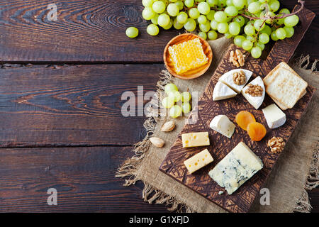 Assortment of cheese with honey, nuts and grape - Stock Photo