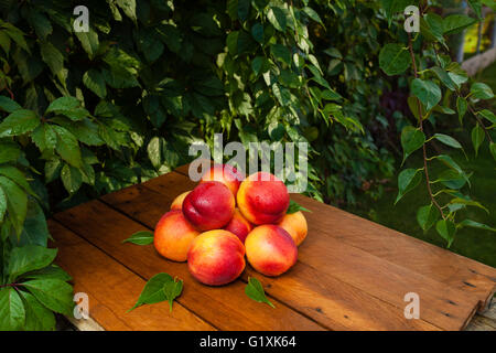 Few peaches and water drops on a wooden table and fallen autumn leaves - Stock Photo