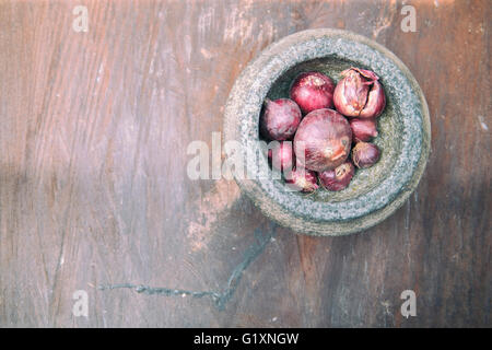 The red onion and stone mortar on old wooden. - Stock Photo