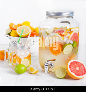 Detox fruit infused flavored water, lemonade, cocktail in a beverage dispenser with fresh fruits - Stock Photo
