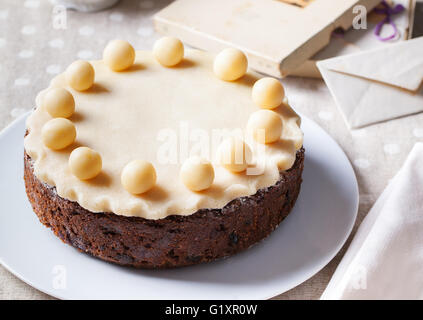 Traditional English Easter cake with marzipan decoration on a white plate. - Stock Photo